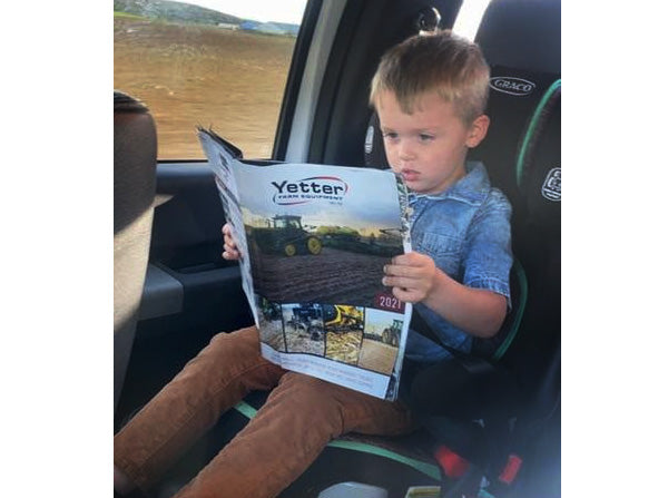 young boy reading Yetter book