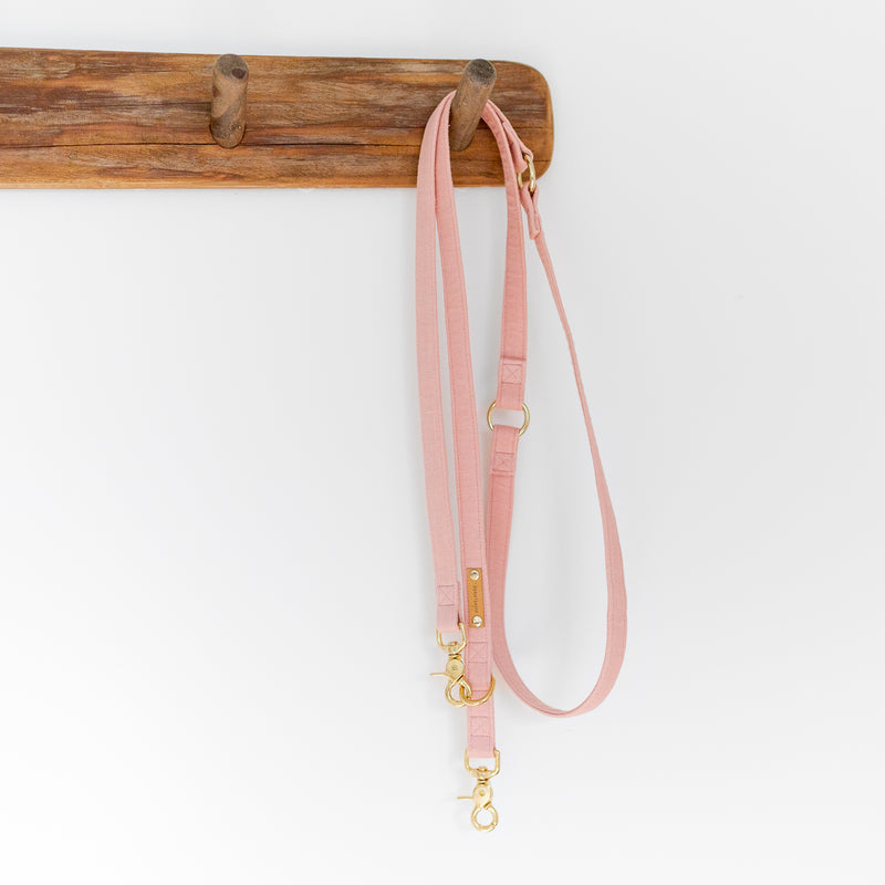 Pastel pink convertible dog leash on a wooden hanger