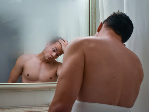 man checking hair growth in the mirror
