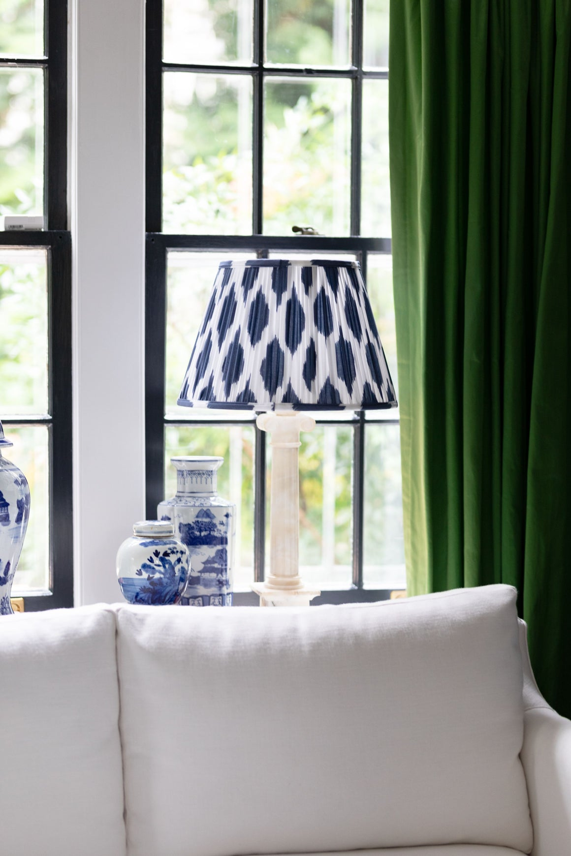Blue lamp shade in front of green curtains.