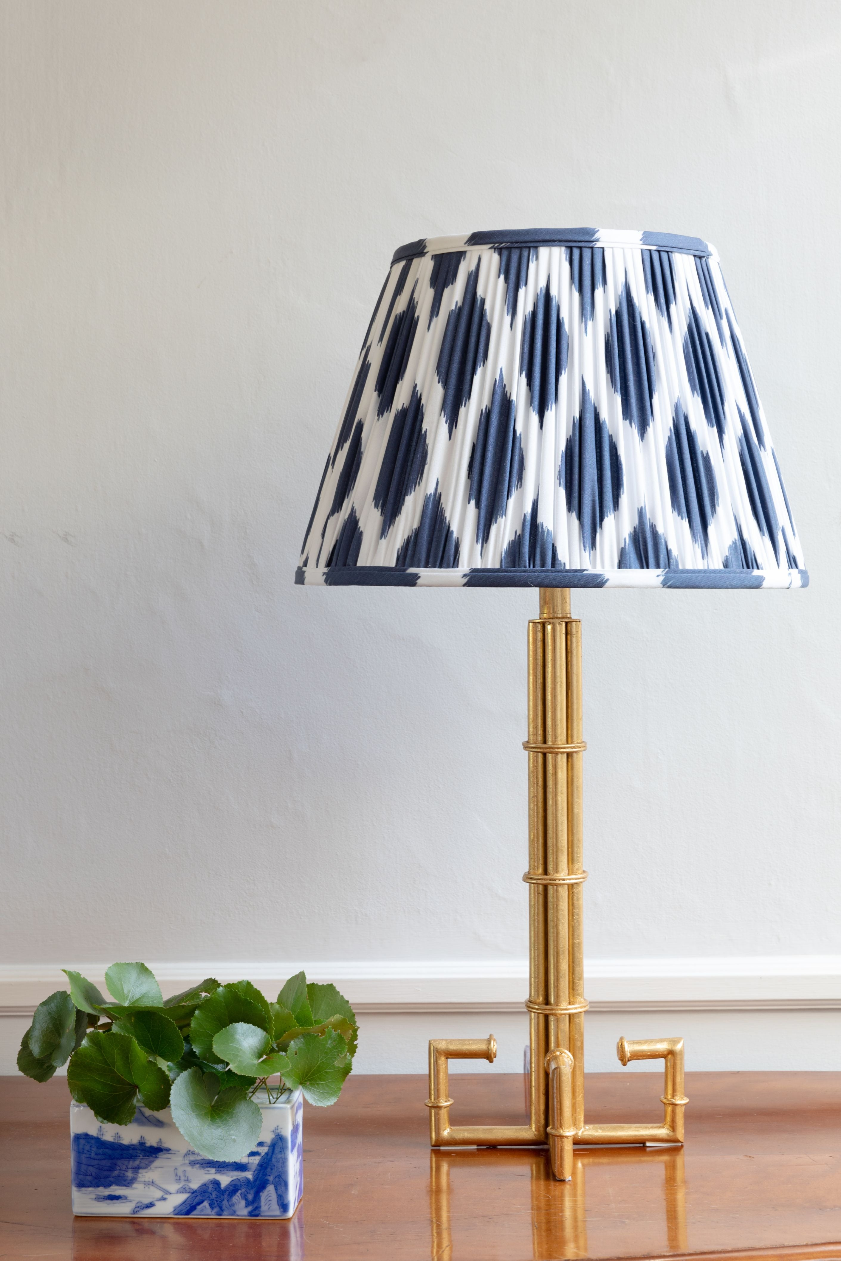 Navy blue patterned lamp shade on bronze stand.