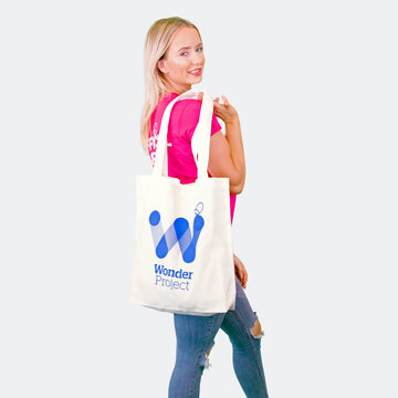 woman with wonder project tote bag