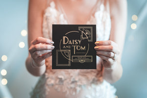 bride holding art deco inspired wedding invitation