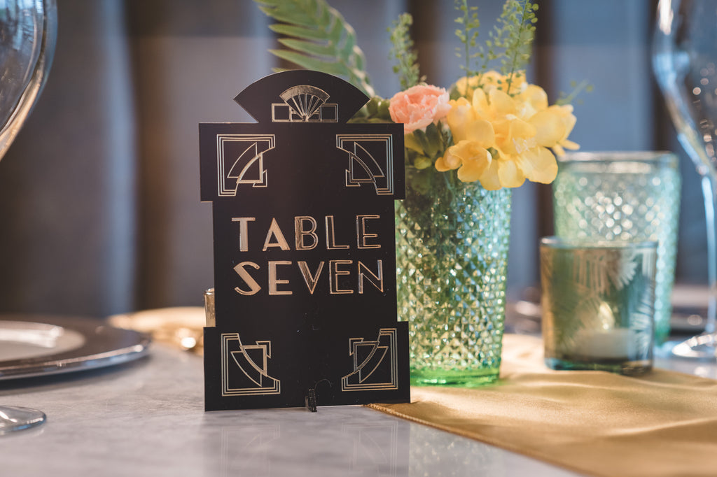 Black and gold plaque with words table seven