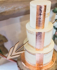 Wooden arrow cake decoration shooting through copper detailed three tier cake
