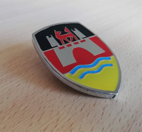 <p>VW Wolfsburg Castle Crest front hood enameled emblem / badge with German flag colors. Comes with a custom bolt type post a