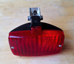 <p>NOS old school vintage rear fog light / stop light assembly complete with mounting bracket.