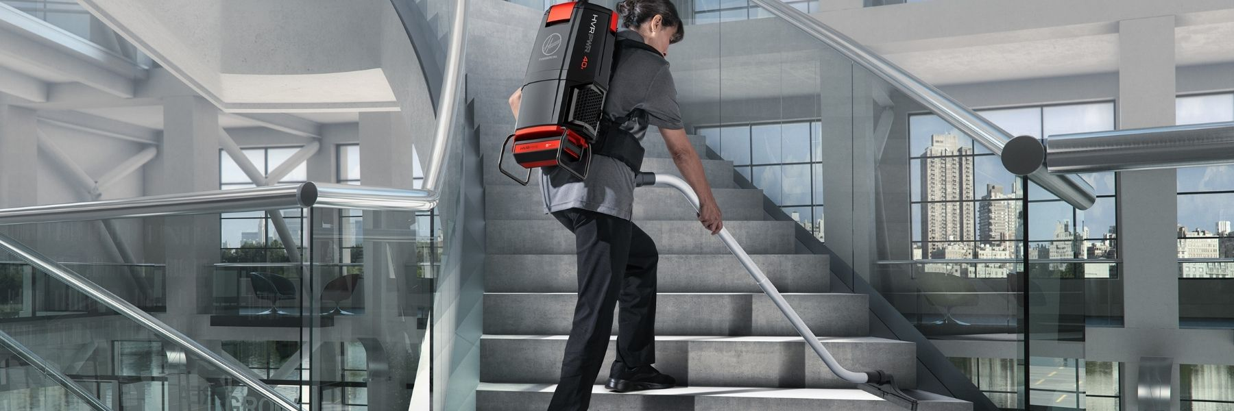 A woman using a Hoover cordless backpack vacuum to clean a stairway.