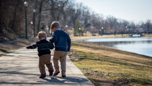 2 brothers walking in a park next to a pond