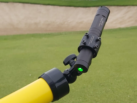 YellowDog  green laser unit shown with ring collar holding unit and double ball 360 swivel unit with lock thumb .Laser is switched on showing green laser dot.