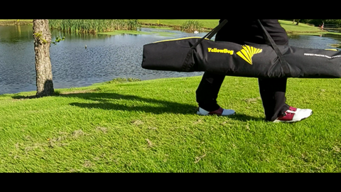 YellowDog golf putting training aid carrier bag being carried by  walking man on his shoulder golf course with lake in back ground in bright sun shine. Image only showing man from waist down. .