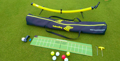 YellowDog Putting Training aid with laser attached placed on putting green beside YellowDog black carrier with yellow logo displayed placed beside Arc putt traing mat with coloured golf balls and battery charger with service allen keys