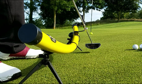 YellowDog putting training aid .Displaying putter in motion and the operation of YellowDog putting training aid on a contoured putting green with golf ball in motion heading toward the golf hole with flag  stick in back ground.