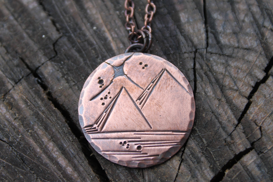 Two pyramids stamped onto copper disc necklace with bright star