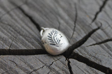 Load image into Gallery viewer, Hemlock Leaf on silver river rock charm