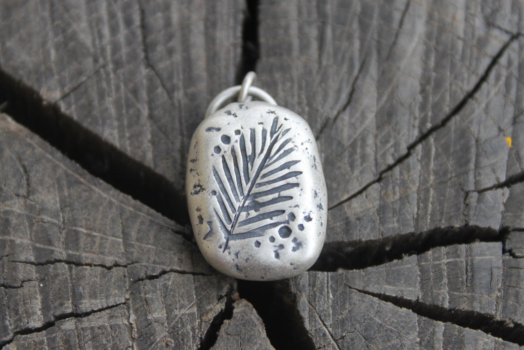 Palm Leaf Stamped onto silver river rock charm