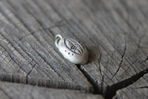 leaf stamped on river rock shaped silver charm