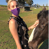 Women petting horse with purple mask
