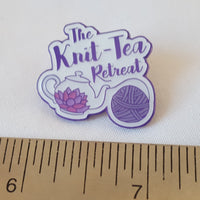 Image shows a Knit-Tea Retreat pin badge featuring the logo, sitting above a metal ruler which shows that it measures approximately one inch.