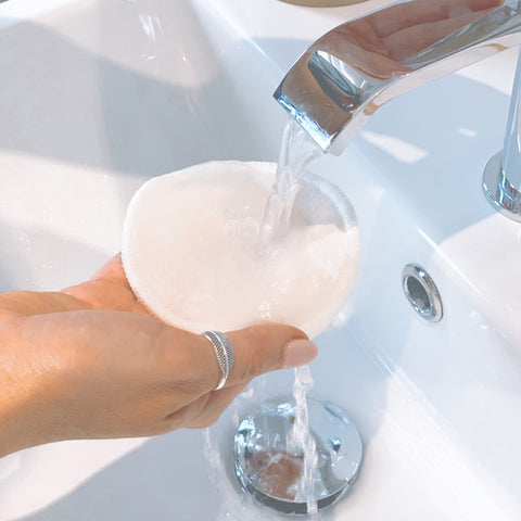 Mooju reusable facial cleansing pad being washed under tap
