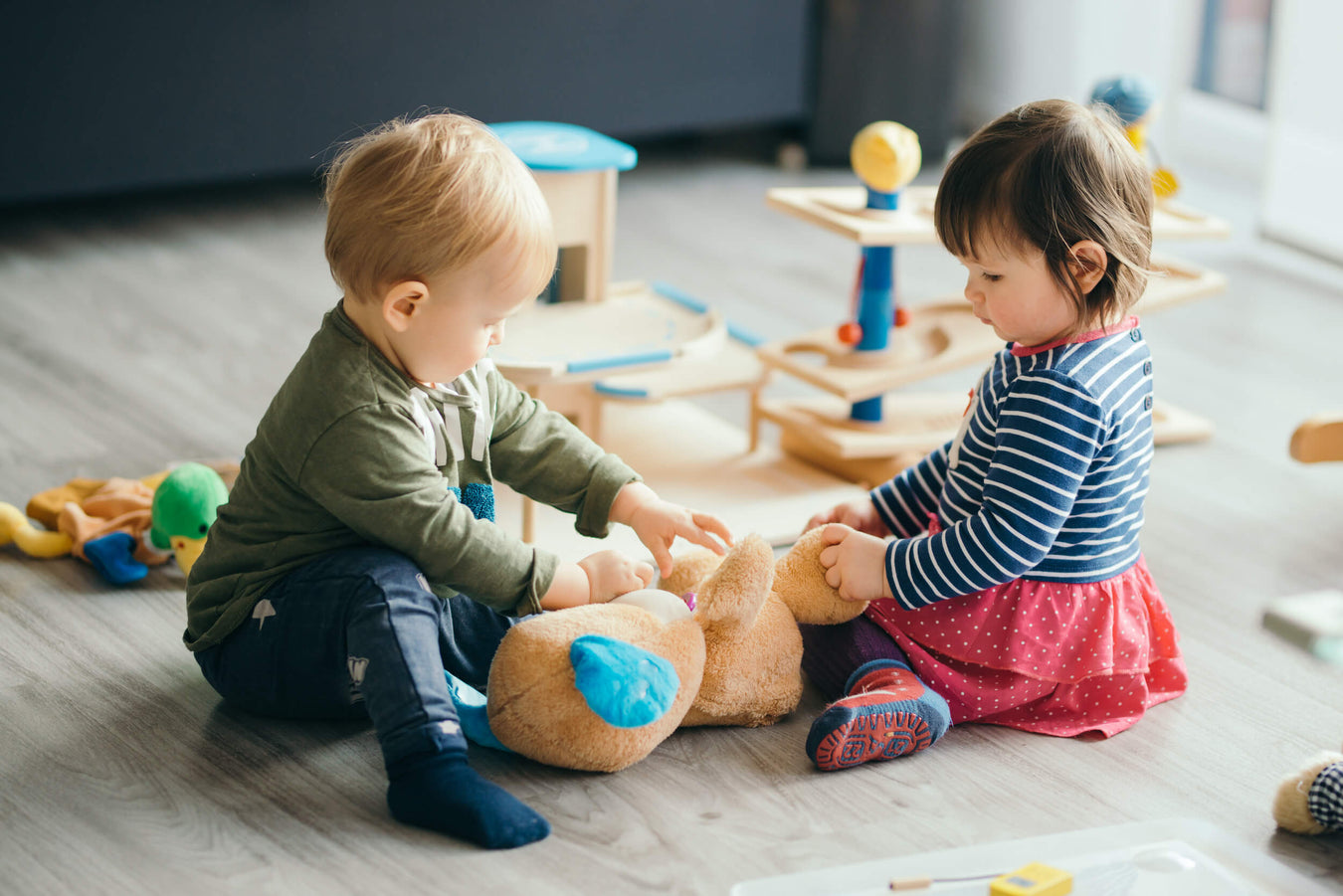 A baby boy and baby girl both wearing colourful second hand outifts play with a teddy bear