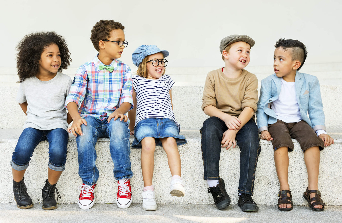 Five kids wearing recircled kids clothes sit and laugh on a bench