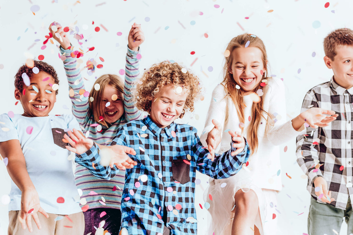 Kids wearing stylish second hand outfits throw confetti in the air to get the party started
