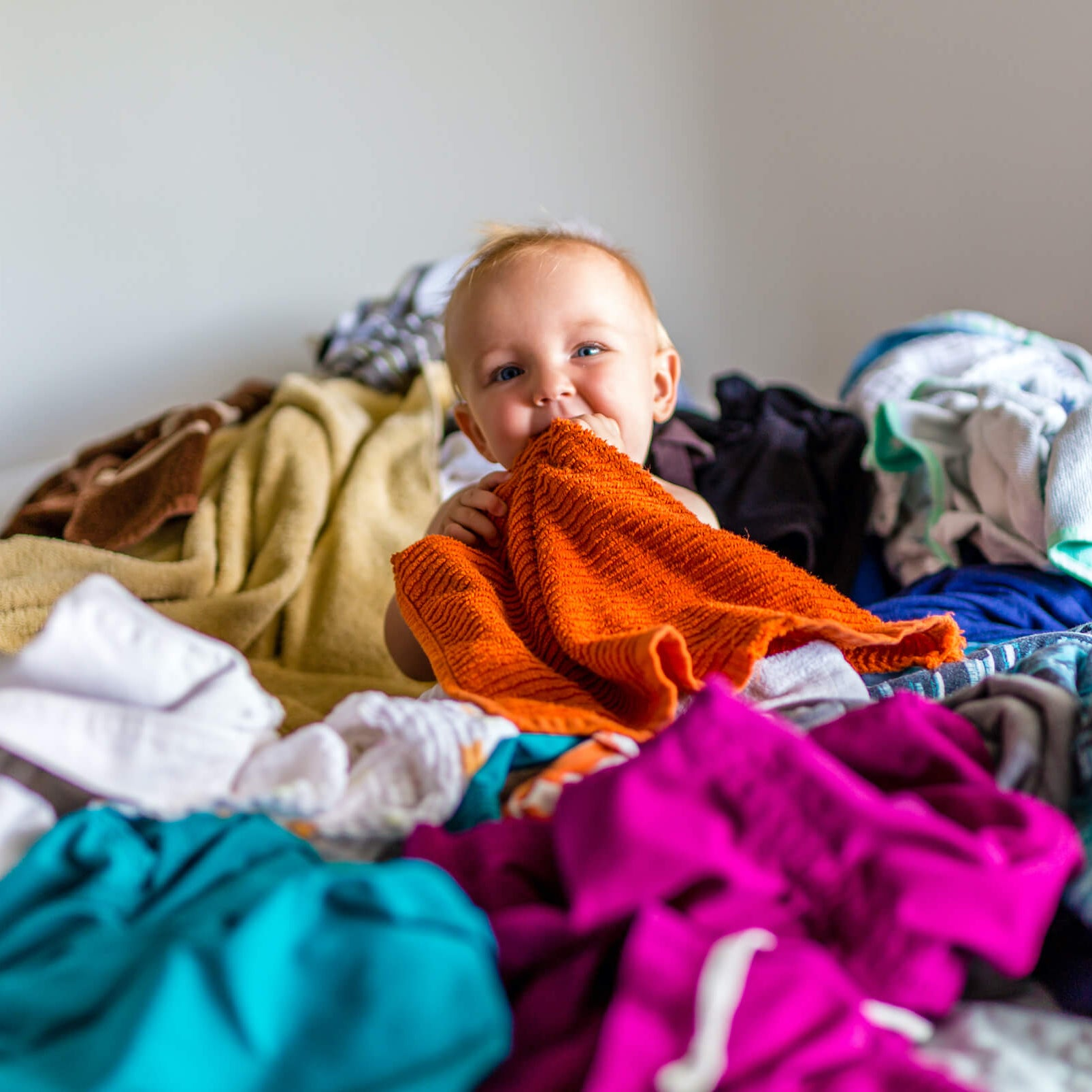 A baby plays in a pile of second hand baby clothes