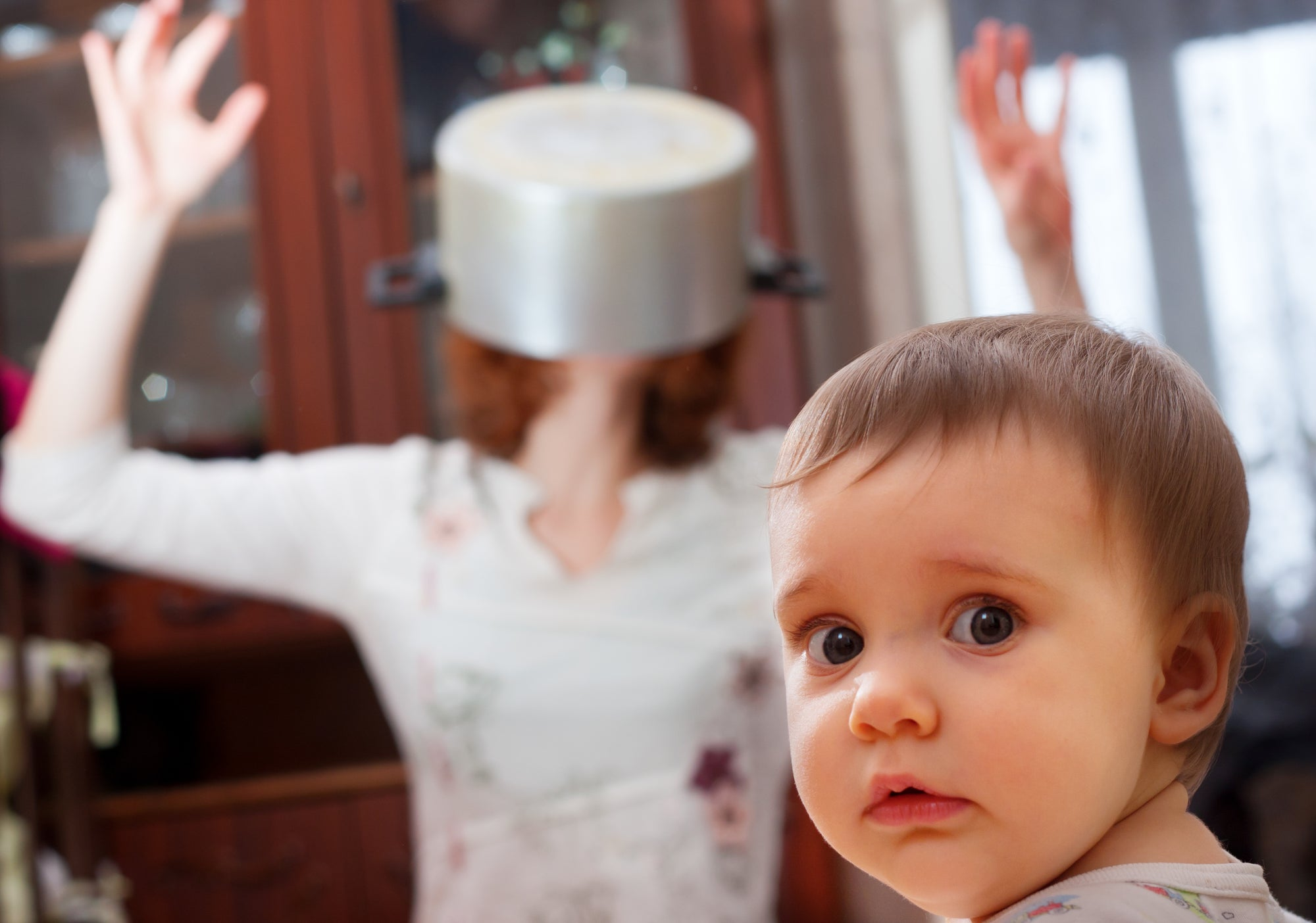 Toddler looks at us as mother is stressed in the background with a pot over her head.