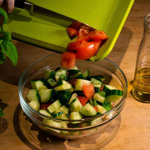 Edge Design's Green Medium Foldable Cutting Board tossing vegetables in pot