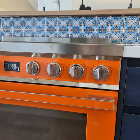Orange range cooker with Alhambra tile splashback