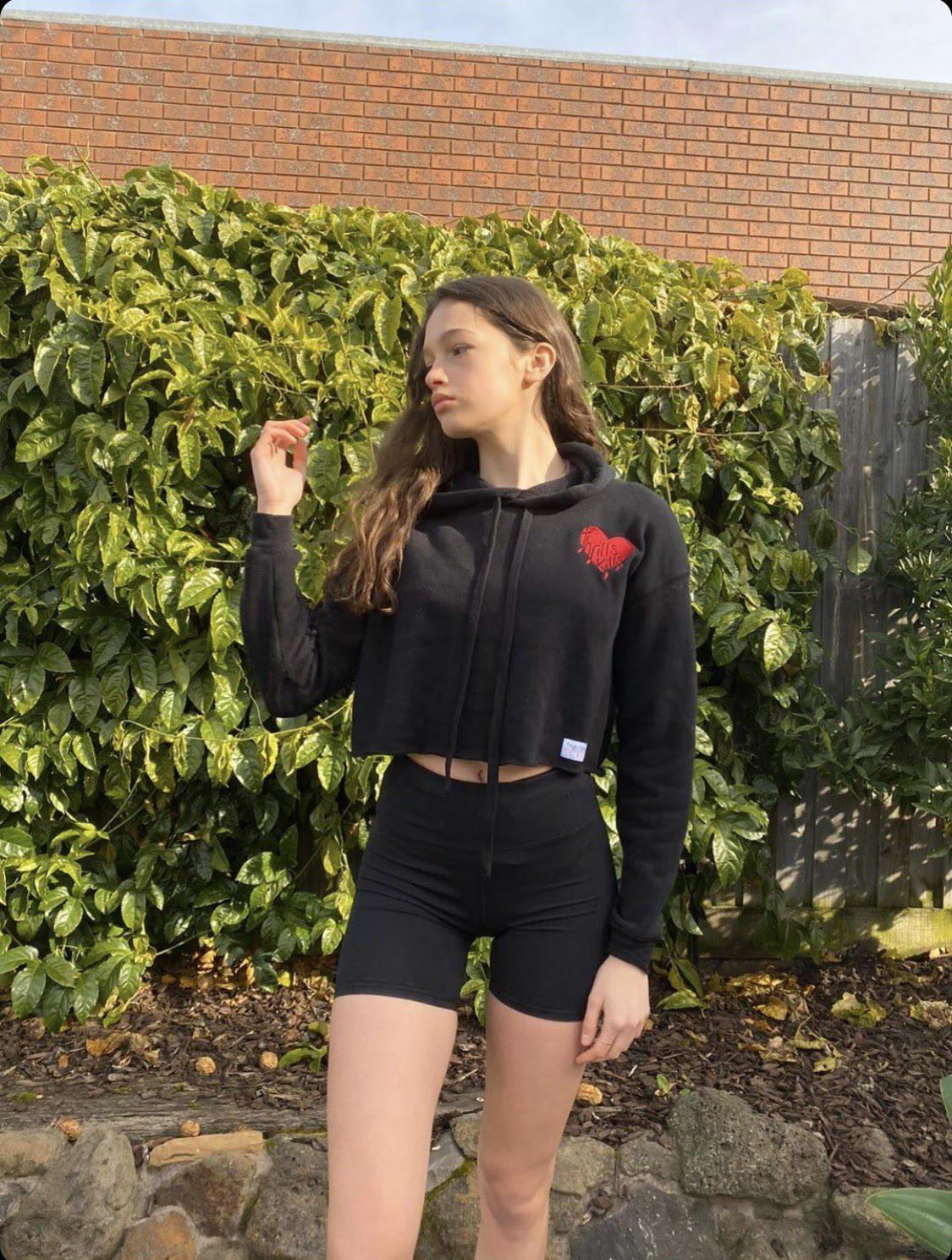 Model pictured showing off her long skinny legs is wearing a Supreme Black Embroidered Love Heart Crop Fleece Hoodie in a garden with green plants in background