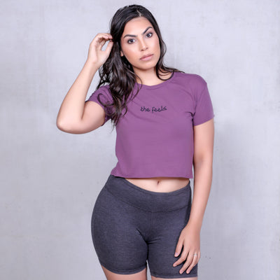 Kim Kardashian look a like modelling wearing the Plum Arabic Script Crop in bike shorts on a plain background