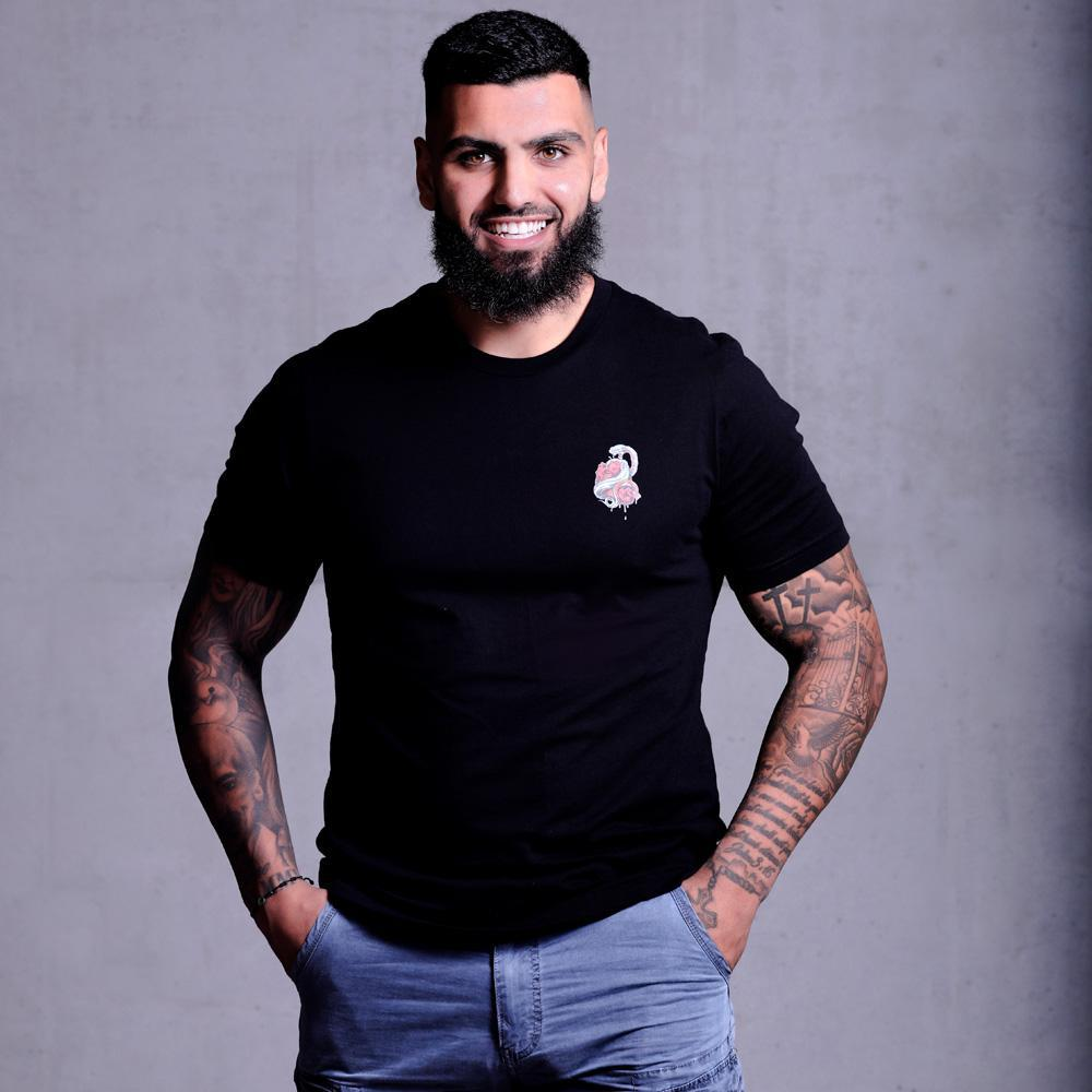Hot middle eastern guy with tattoos and a beard modelling wearing Supreme Black Snakes T-shirt with a snake wrapped around a heart dressed with short jeans