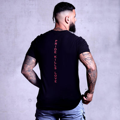Hot middle eastern guy with tattoos and a beard modelling wearing Supreme Black Snakes T-shirt with short jeans from back with a printed 'pride kills love' down the spine in red font