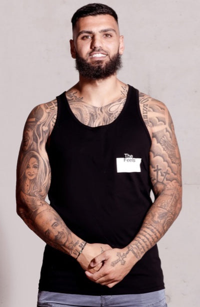 middle eastern guy with beard and faded hair cut and tattoos wearing Supreme Mens White Muscle Singlet with a ying yang design showing off his tattoos and muscles