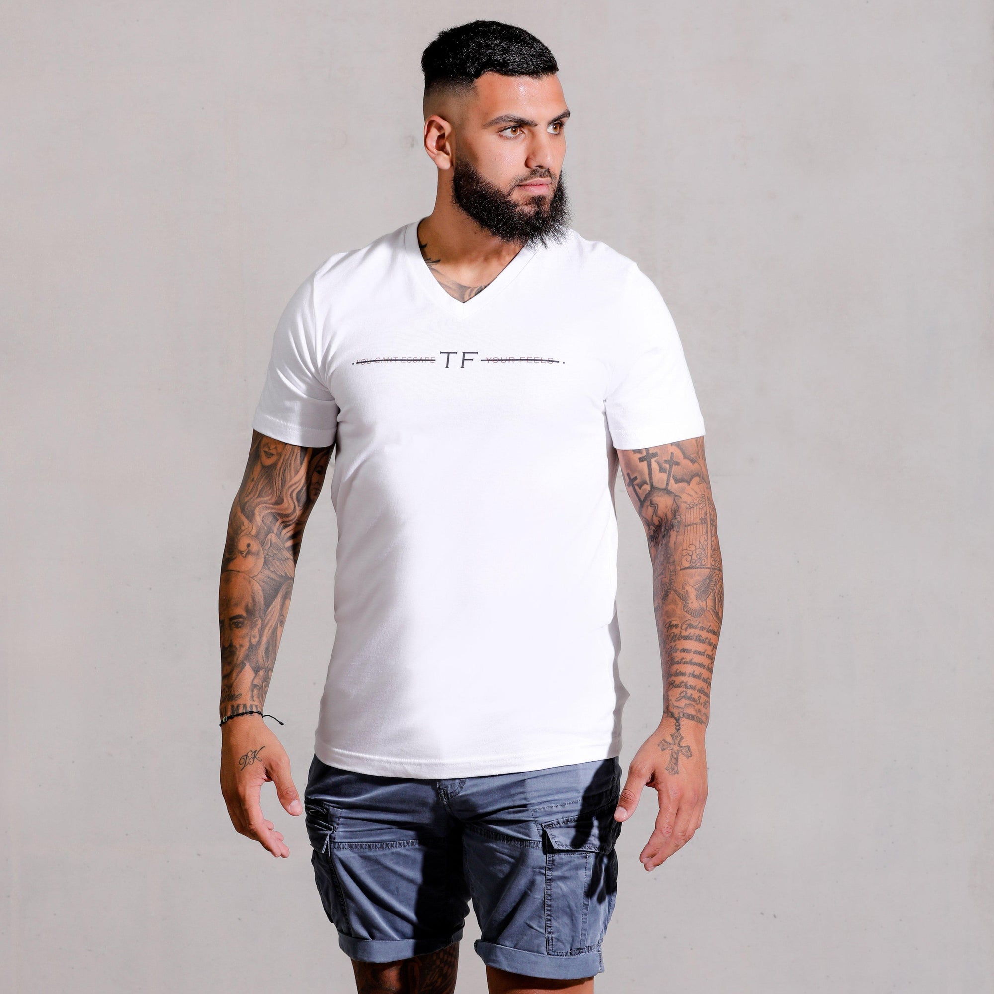 Muscle hunk with tattoos and beard modelling wearing White V Neck Signature Escape T-shirt and jeans for a causal look. Printed on the chest is the feels apparel signature slogan.