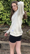 Model wearing White Embroidered Fleece Hoodie showing the design on the front and back and ribbed style on side