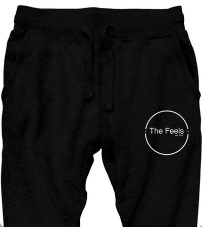 Close up of Supreme Black Sweatpants With Embroidered Logo and white embroidery on left side with a plain background