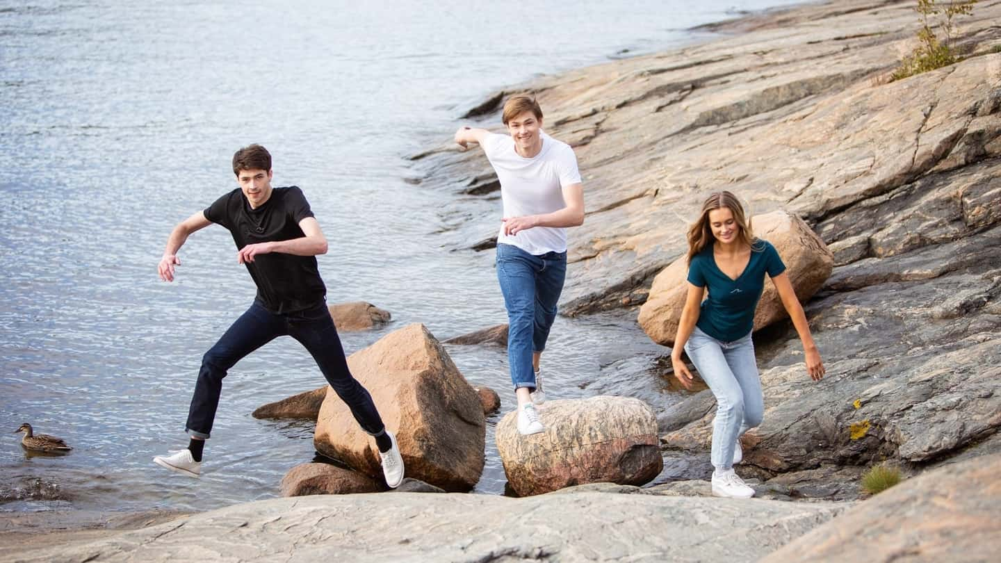 Happy wavemakers jumping by the ocean in Oceanness eco t-shirts