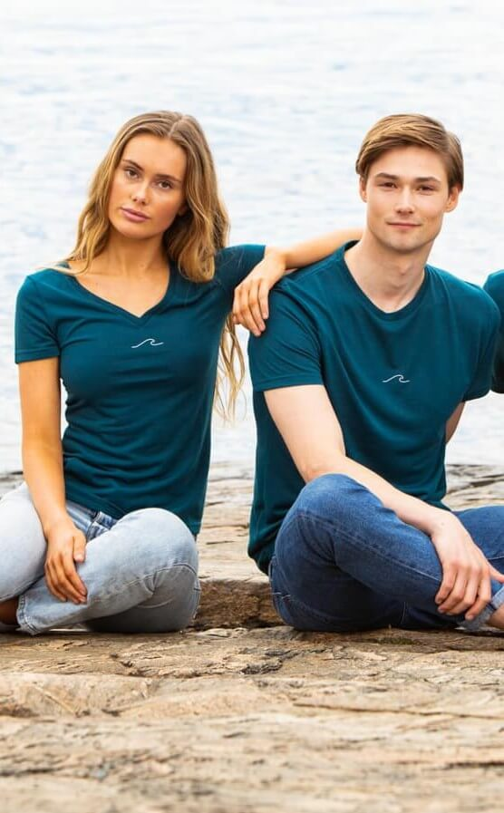 Man and woman in Oceanness t-shirt in Ocean Green by the ocean