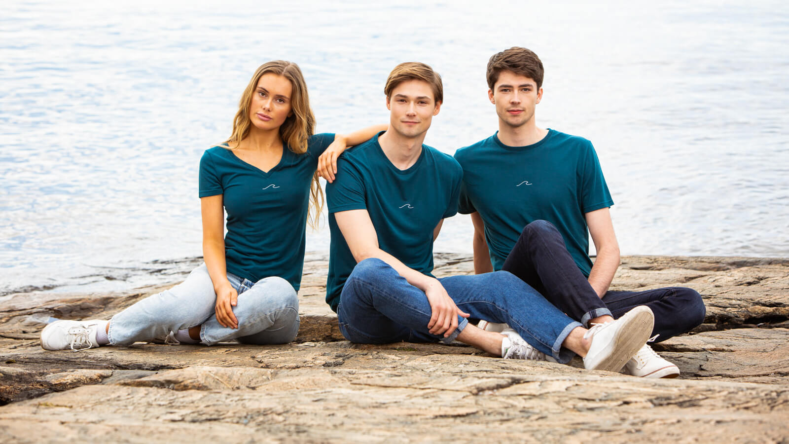 Models posing by the ocean in Eco Oceanness T-Shirts in Ocean Green