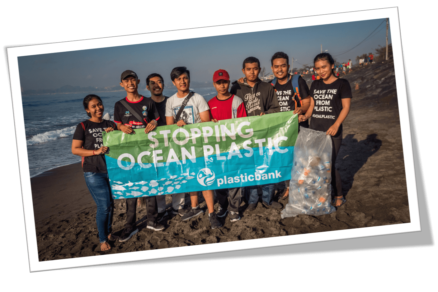 Plastic collectors posing with Stopping Ocean Plastic sign by the Plastic Bank