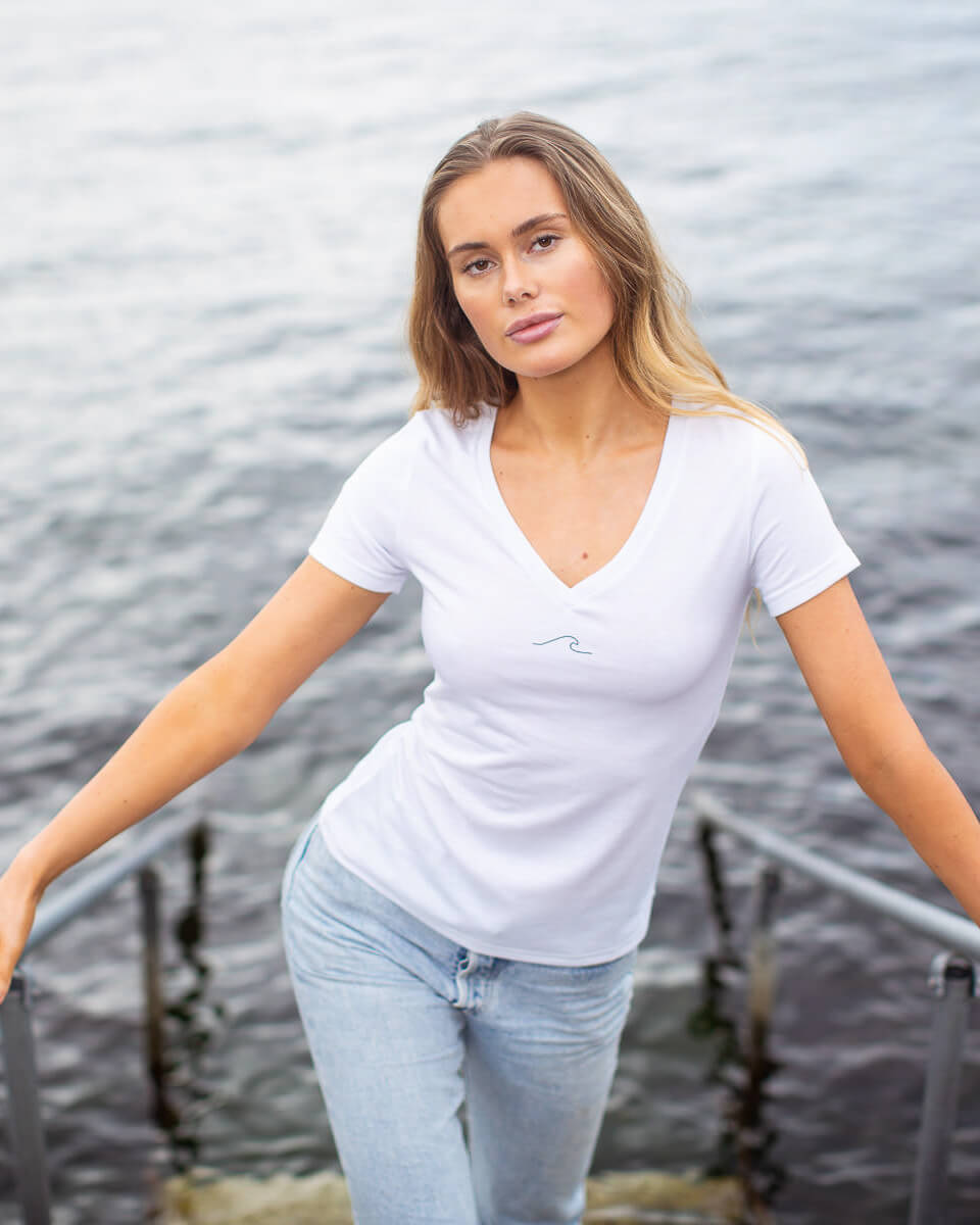 Model posing in eco-friendly Oceanness t-shirt with wave in Arctic White
