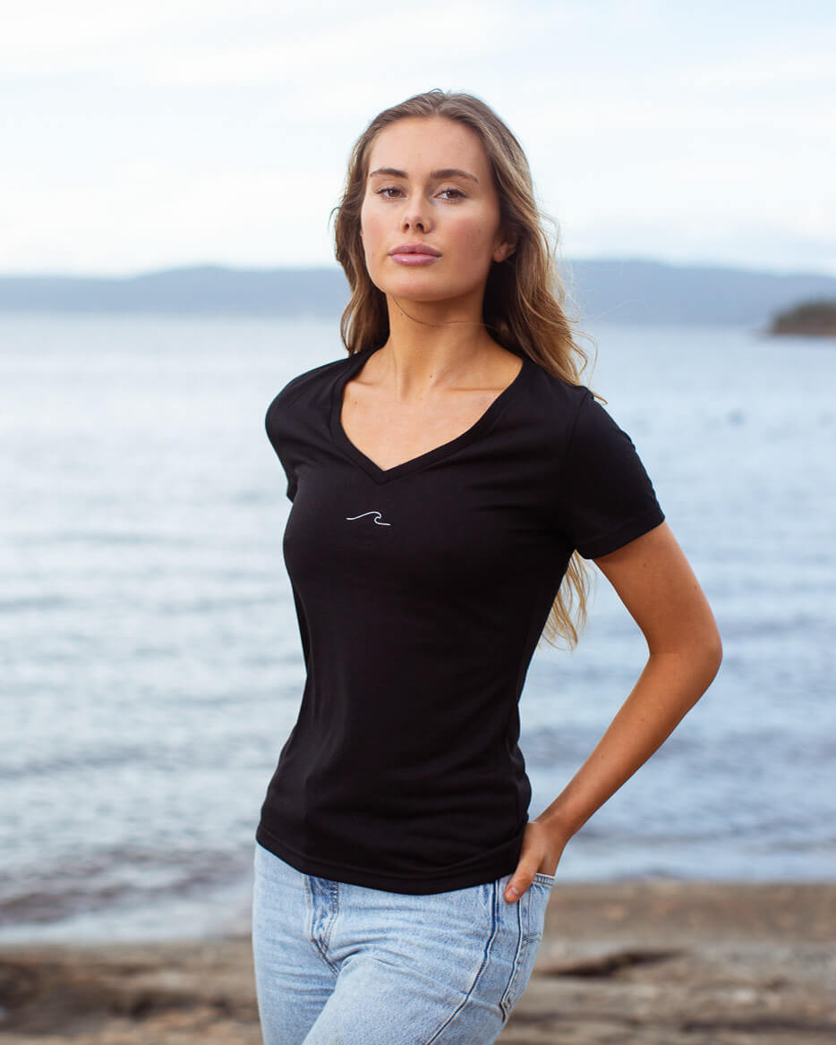 Model posing in eco-friendly Oceanness t-shirt with wave in Midnight Black