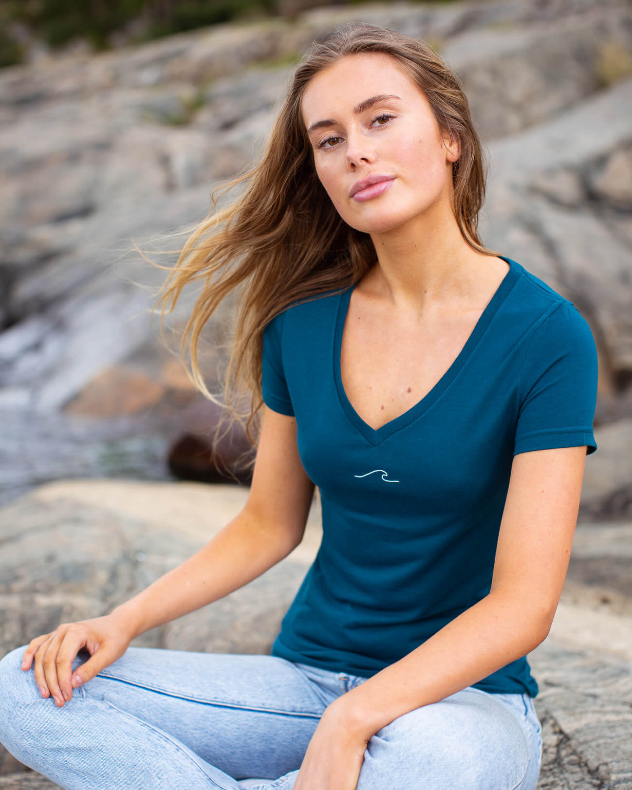 Model posing in eco-friendly Oceanness t-shirt with wave in Ocean Green