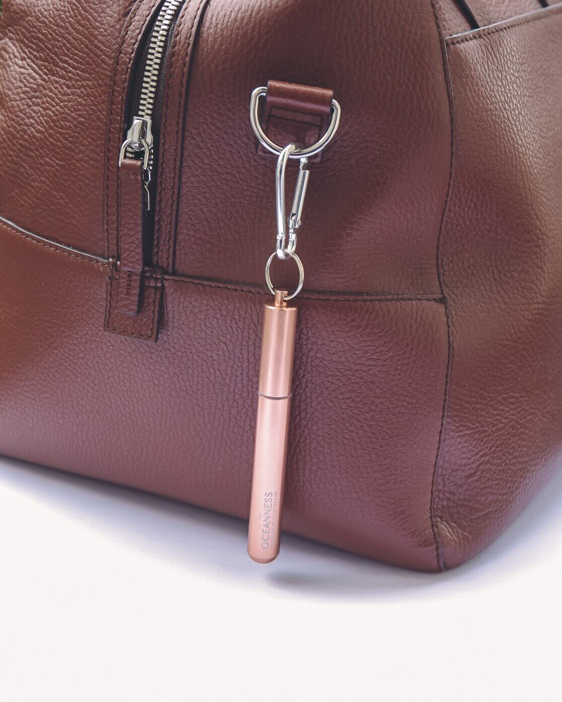 Oceanness rose gold reusable travel straw hanging on a bag with carabiner