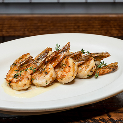 Five grilled shrimp served on a white oval platter.