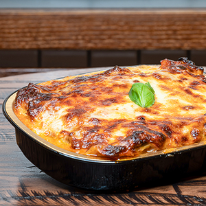 Lasagna bolognese served in a black casserole dish garnished with basil.