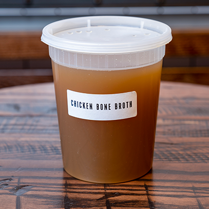 Plastic quart container of chicken bone broth.